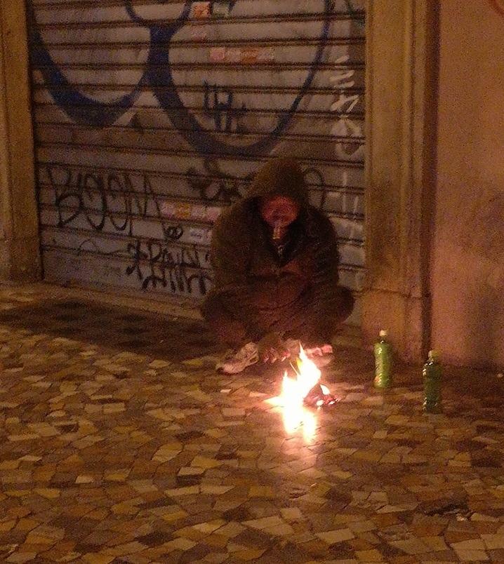 Godenzio si riscalda accendendo il fuoco sotto ai portici di Piazza Vittorio